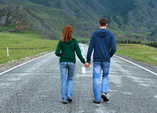 Couple walking Altai road. Young happy couple (caucasian men and woman) walking along the asphalt road among beautiful mountain area (Altai territory, Russia) Royalty Free Stock Images