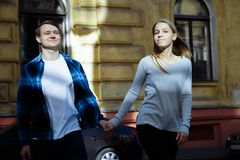 Couple walking around the city holding hands, a date, love and relationships. royalty free stock images