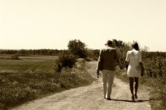 Couple walking away. Stylish couple walking away in nature, cross-processed photo Stock Photo