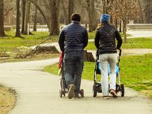 Couple Walking With Baby Strollers Through A Path In A Park stock photos