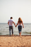 Couple walking on a beach Stock Images