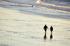 Couple walking at the beach Stock Image