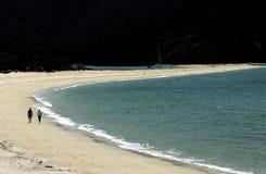 Couple walking on beach. Awaroa Bay, Abel Tasman National Park, New Zealand Royalty Free Stock Photos