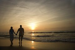 Couple walking on beach stock photo