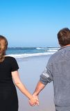 Couple walking on the beach. Young married couple walking hand-in-hand on the sandy beach on their winter holiday in South Africa. Shot on a sunny day with blue Stock Photo
