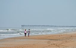 Couple walking on beach. Rear view of couple walking on sandy beach with waves and long pier in background Stock Image
