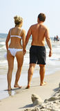 Couple walking on beach. Rear view of young couple walking on sandy beach with sea in background Stock Photo