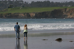 Couple walking on the beach. Enjoying a beautiful day at pebble beach in California Royalty Free Stock Photography