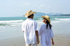 Couple Walking on Beach. Couple of lovers in white clothes and straw hats are walking on the beach Stock Photography