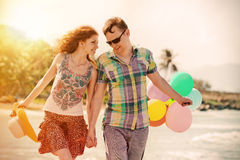 Couple walking on the beach with air colored balls. Royalty Free Stock Photos
