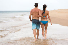 Couple walking beach. Back view of couple walking on beach together Stock Image