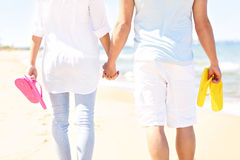 Couple walking at the beach and carrying flip flop Stock Photography