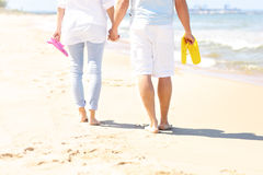 Couple walking at the beach and carrying flip flops Royalty Free Stock Image