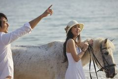 A couple walking on beach. A Chinese couple walking on beach with horses Stock Photo
