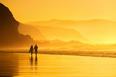 Couple walking in the beach. At the sunset royalty free stock photo
