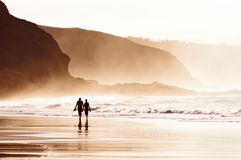Couple walking on beach with fog Royalty Free Stock Photo