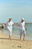 Couple walking on beach Stock Images