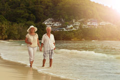 Couple walking on  beach. Happy elderly couple walking on  tropical beach Stock Photography