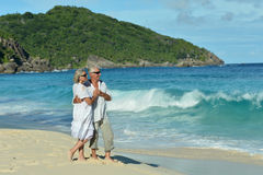 Couple walking on  beach. Happy elderly couple walking on  tropical beach Stock Image