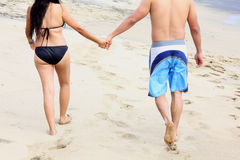 Couple walking the beach holding hands Stock Photography