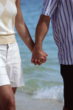 Couple walking on beach holding hands Royalty Free Stock Image