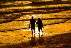 Couple walking on beach. Couple walking holding hands on golden sunset beach
