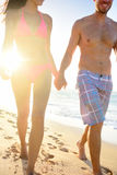 Couple walking on beach holding hands man smiling. Young couple walking in beach sunset happy holding hands men smiling on joyful honeymoon vacation Hawaii Stock Photos