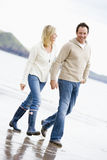 Couple walking on beach holding hands smiling stock photos