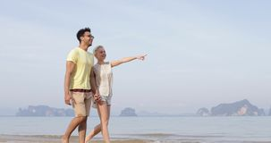 Couple Walking On Beach Holding Hands Talking, Young Man And Woman Point Finger, Tourists On Vacation