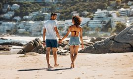 Couple walking on beach holding hands royalty free stock photo