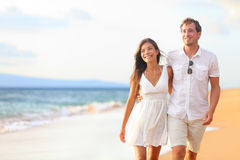 Couple walking on beach on romantic travel. Honeymoon vacation summer holidays romance. Young happy lovers, Asian women and Caucasian men holding hands Stock Images