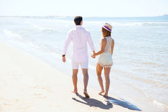 Couple walking at the beach on a sunny day Stock Image