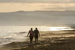 couple walking on the beach at sunrise royalty free stock images