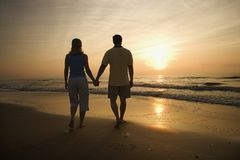 Couple walking on beach at sunset. stock photo