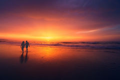Couple walking on beach at sunset Royalty Free Stock Photos