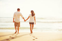 Couple Walking on the Beach at Sunset Royalty Free Stock Photography