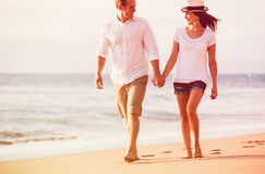 Couple Walking on the Beach at Sunset Royalty Free Stock Image