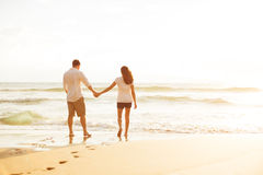 Couple Walking on the Beach at Sunset Stock Photos