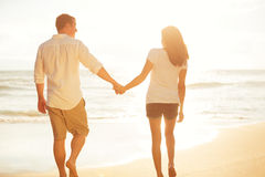 Couple Walking on the Beach at Sunset Royalty Free Stock Photo