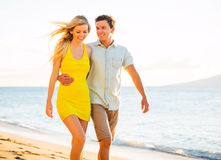 Couple Walking on the beach at Sunset, Romantic Vacation. Attractive Happy Couple Walking on the beach at Sunset, Romantic Vacation Royalty Free Stock Photography