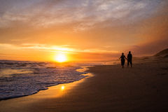 Couple walking on beach at sunset. Silhouette royalty free stock photo