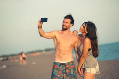 Couple walking on beach at sunset taking selfie picture Royalty Free Stock Images