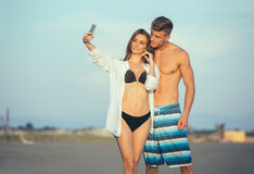 Couple walking on beach at sunset taking selfie picture. On mobile phone relaxing together Royalty Free Stock Photos