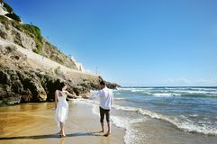 Couple walking on beach together holding hands Stock Photography