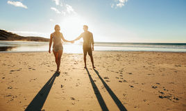 Couple walking on the beach together at sunset Royalty Free Stock Images