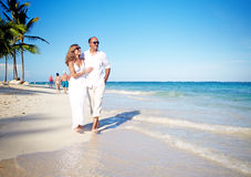 Couple walking on the beach. Tropical resort vacation Stock Image