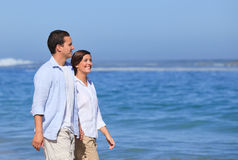 Couple walking on the beach under the sun Royalty Free Stock Images