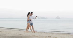 Couple Walking On Beach Using Cell Smart Phones Embracing Talking, Young Man And Woman Tourists Networking Online. Slow Motion 60 stock footage