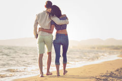 Couple walking on beach. Young happy interracial couple walking on beach smiling holding around each other. stock photo