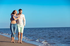 Couple walking on beach. Young happy interracial couple walking on beach. Royalty Free Stock Photos
